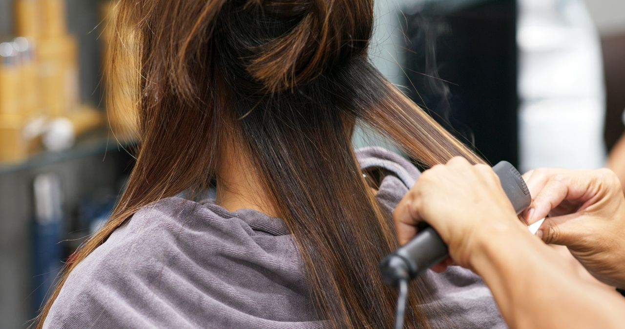 femme qui se lisse les cheveux avec une brosse